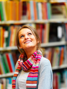 Young smiling woman looking upwards in library